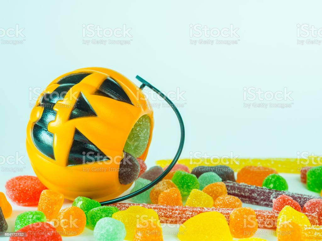 Trick or treat halloween bucket filled with colorful candies on white background royalty-free stock photo