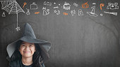 istock Trick or treat halloween girl kid having fun in witch hat black costume with funny doodle of spider web, jack o lantern and party decoration on spooky school chalkboard background 1021952574