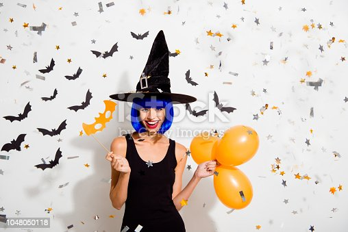 1016084100istockphoto Trick or treat I can't choose! Portrait of dream, dreamy lady hold three orange ballons and paper mask on stick, make big hollywood smile isolated on white background 1048050118