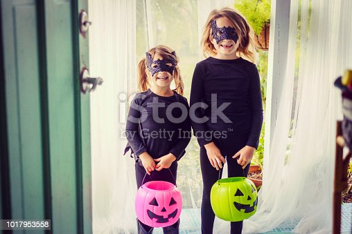 Two cute kids in bat costumes dressed up for Halloween at the front door of a domestic home, matching and super cute in costumes with pumpkin containers for collecting candy