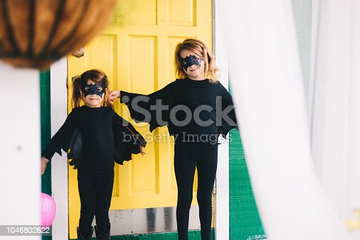 Two cute kids in bat costumes dressed up for Halloween at the bright yellow front door of a domestic home, matching and super cute in costumes with pumpkin containers for collecting candy
