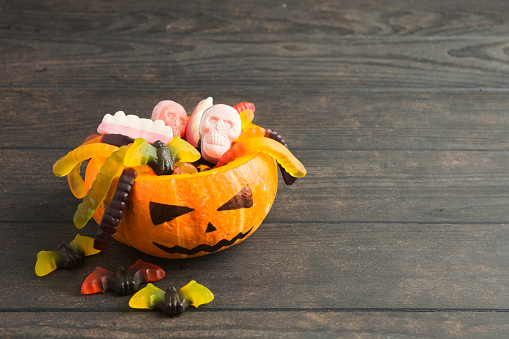 Trick or treat pumpkin jack with colorful candies on wooden background
