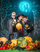 Group funny children dressed in halloween costumes posing against the background with chalk drawing on a Halloween theme