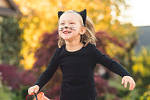 A young girl dressed adorably in a black cat costume runs down the sidewalk with a big smile and a pumpkin bucket as she gets ready to trick or treat.