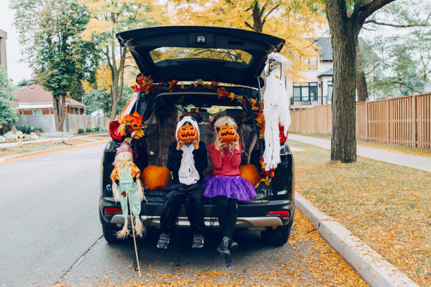 Trick or trunk. Children celebrating Halloween in trunk of car. Boy and girl with red pumpkins celebrating traditional October holiday outdoors. Social distance during coronavirus covid-19. Trick or trunk. Children celebrating Halloween in trunk of car. Boy and girl with red pumpkins celebrating traditional October holiday outdoor. Social distance and safe alternative celebration. halloween covid stock pictures, royalty-free photos & images