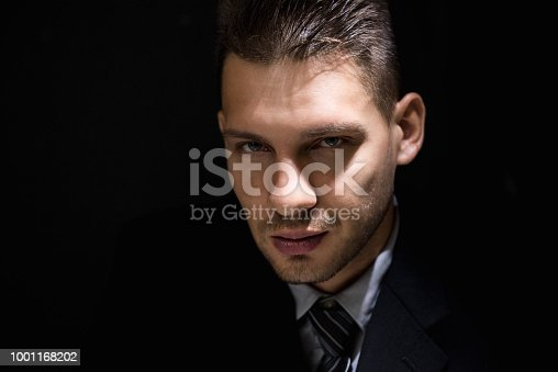 Face of tricky sly man staring at the camera in dark shadow