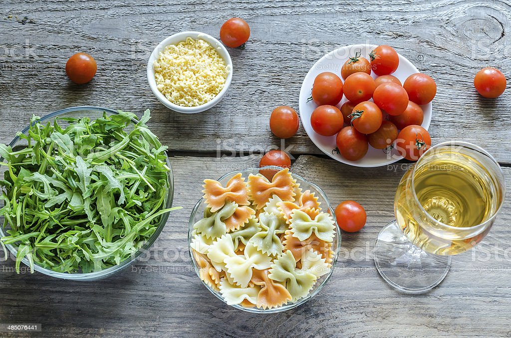 Tricolore farfalle with arugula, parmesan and cherry tomatoes stock photo