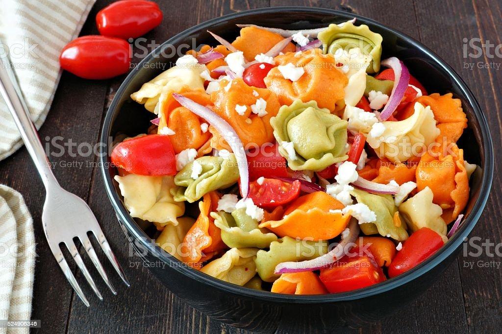 Tricolored tortellini pasta salad on dark wood table stock photo