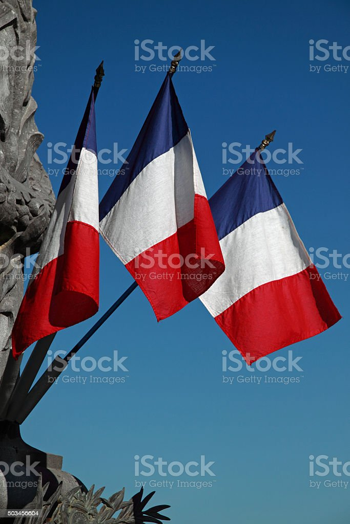 Tricolours on top of a war memorial in SW France stock photo