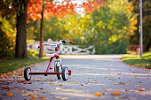 Tricycle in the park on sunset, autumn time, children in the park, enjoying warn autumn day