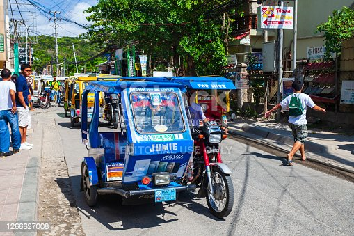 BORACAY, PHILIPPINES - MARCH 04, 2013: Tricycle at the main street in Boracay island. Tricycle is a very popular public taxi transport in Philippines.