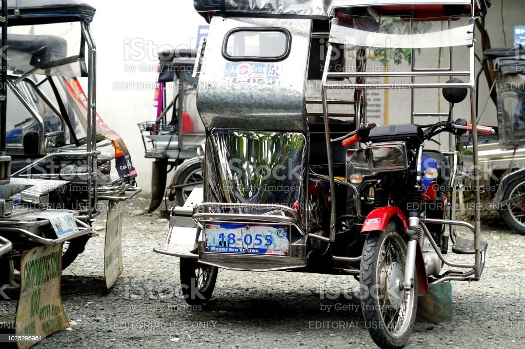 Tricycles at a parking lot waiting in line for their turn to take passengers. stock photo