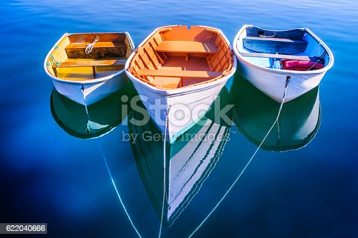 Three rowboats float gently on the quiet waters od Quissett Harboe in Falmouth, Massachusetts on a Autumn afternoon.