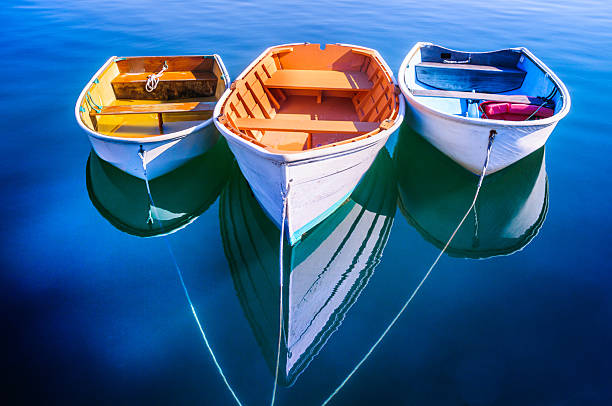Trident of Rowboats Three rowboats float gently on the quiet waters od Quissett Harboe in Falmouth, Massachusetts on a Autumn afternoon. cape cod stock pictures, royalty-free photos & images