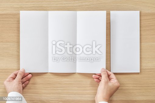 istock Trifold pamphelt mock up flyer brochure design A4 size paper in business man's hand for template illustration mockup, flatlay on wood table from top view 1009741954