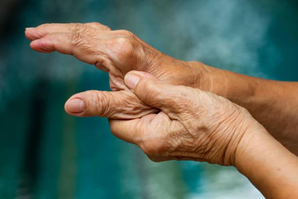 trigger finger, la main gauche de la femme âgée massant son doigt de pouce, souffrant de la douleur, fermez vers le haut - projectile de macro, fond de piscine, syndrome d'office, soins de santé et concept asiatique de corps de massage - maladie photos et images de collection