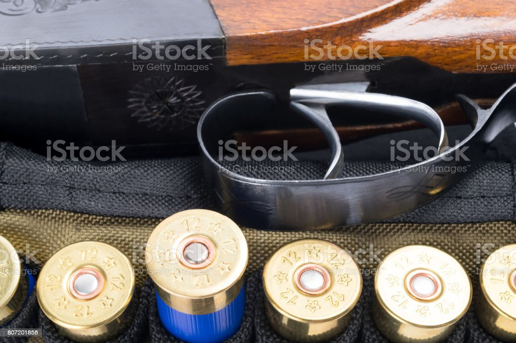 Trigger from a hunting rifle next to cartridges stock photo