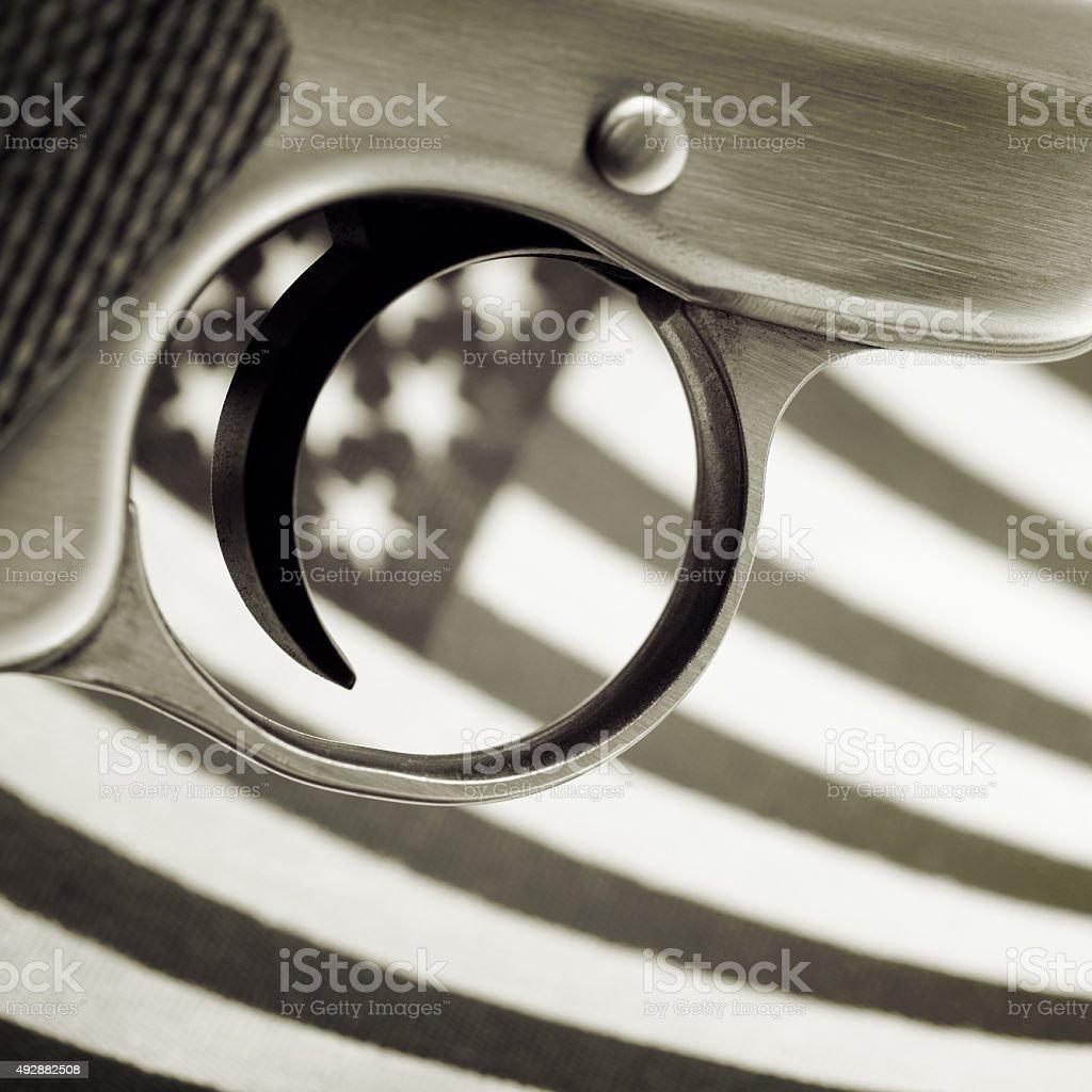 Trigger of Handgun Over American Flag stock photo