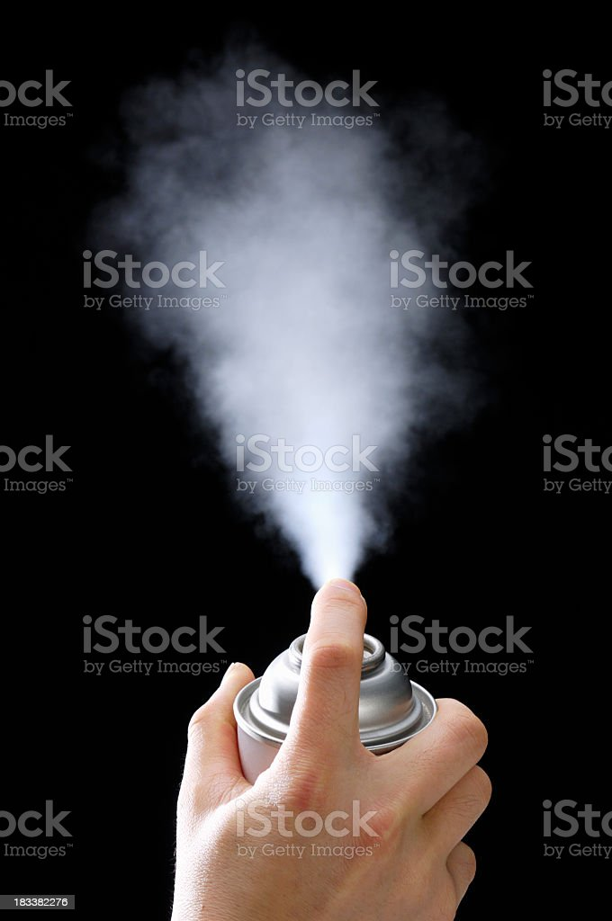 Trigger pressed on aerosol spray can releasing white cloud royalty-free stock photo