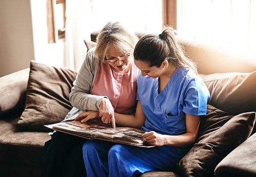 Shot of a nurse and a senior woman looking at a photo album together