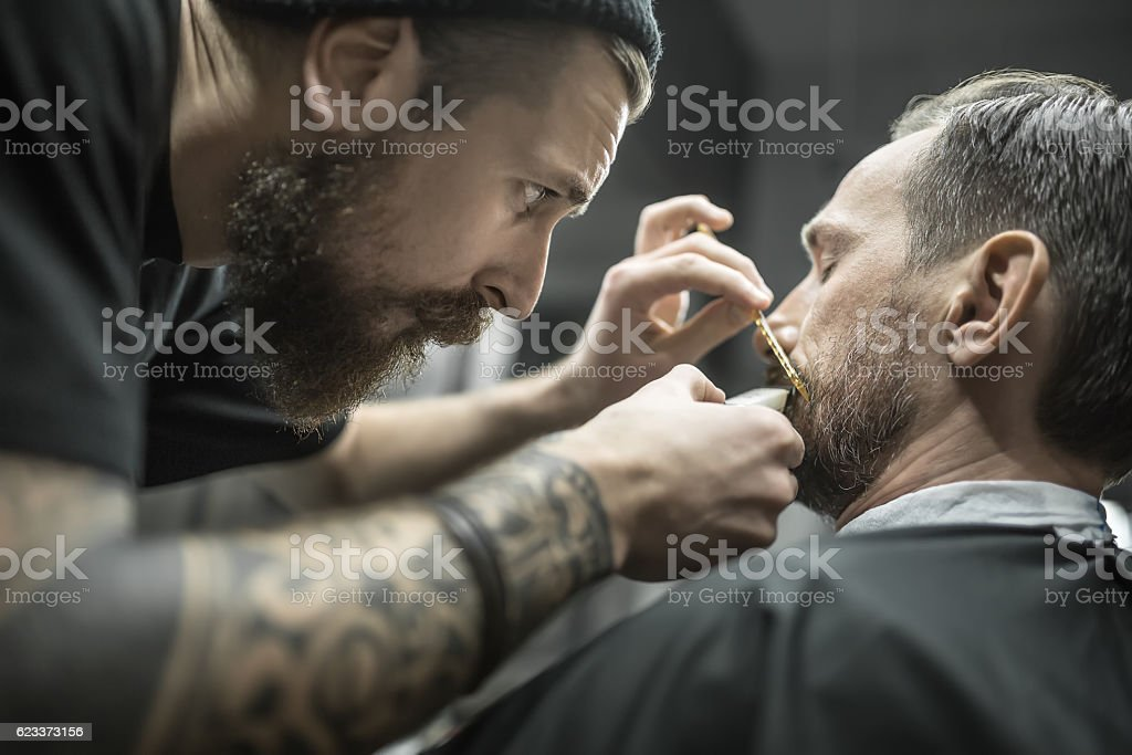 Trimming beard in barbershop stock photo