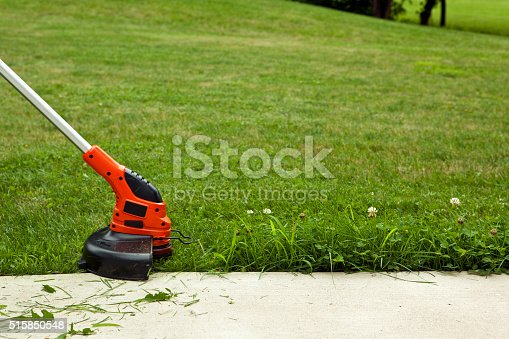 Close-up of a string trimmer cutting the grass along a concrete sidewalk.