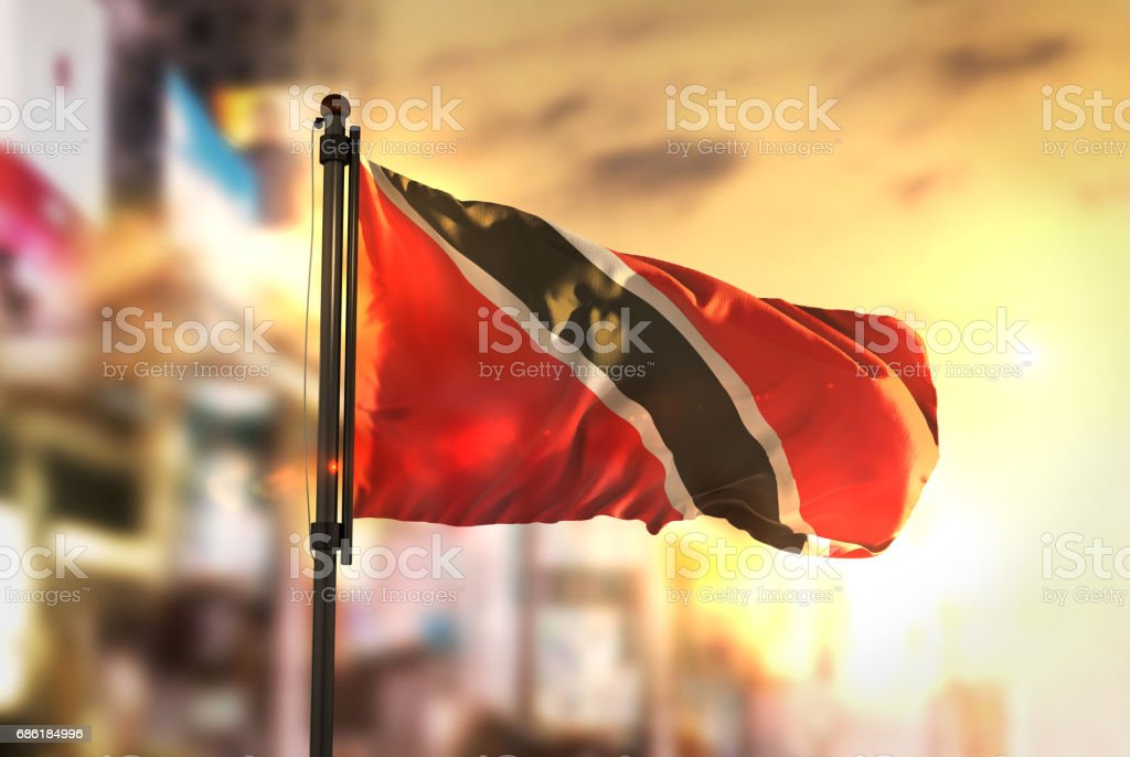 Trinidad and Tobago Flag Against City Blurred Background At Sunrise Backlight stock photo