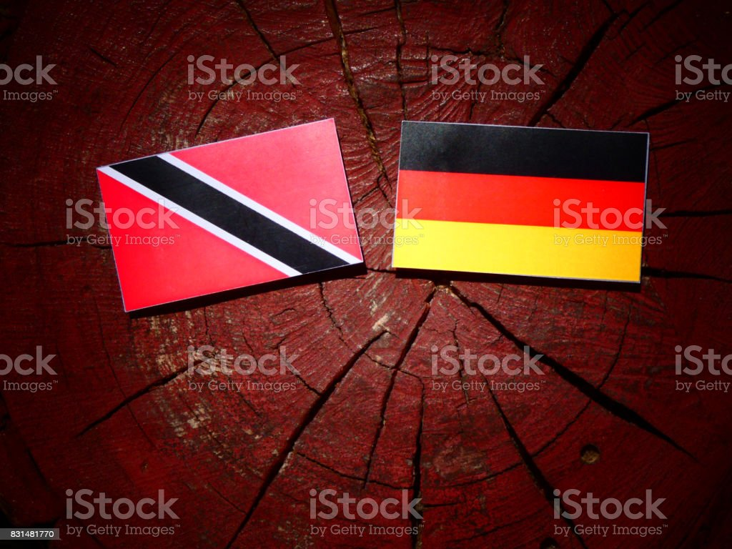 Trinidad and Tobago flag with German flag on a tree stump isolated stock photo
