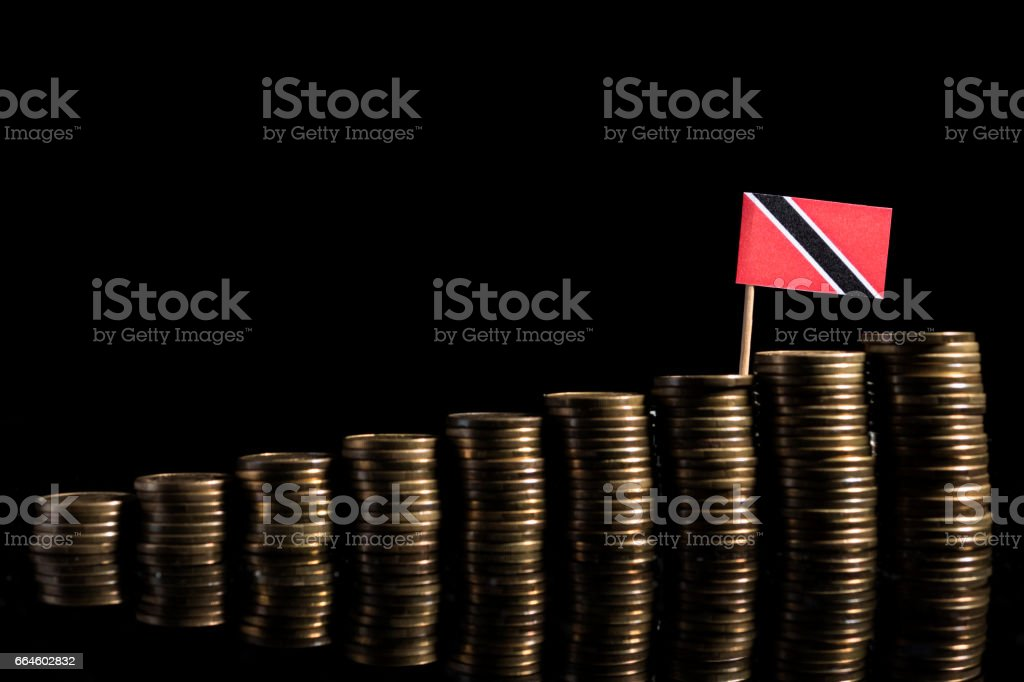 Trinidad and Tobago flag with lot of coins isolated on black background stock photo