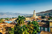 Panoramic view over the city of Trinidad, Cuba with mountains in the background and a blue sky. The bell tower belongs to the Iglesia y Convento de San Francisco.