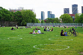 Toronto, Canada - May 31, 2020: Locals walk and relax in the Trinity-Bellwoods park of Toronto on a weekend during coronavirus pandemic in Ontario, Canada.