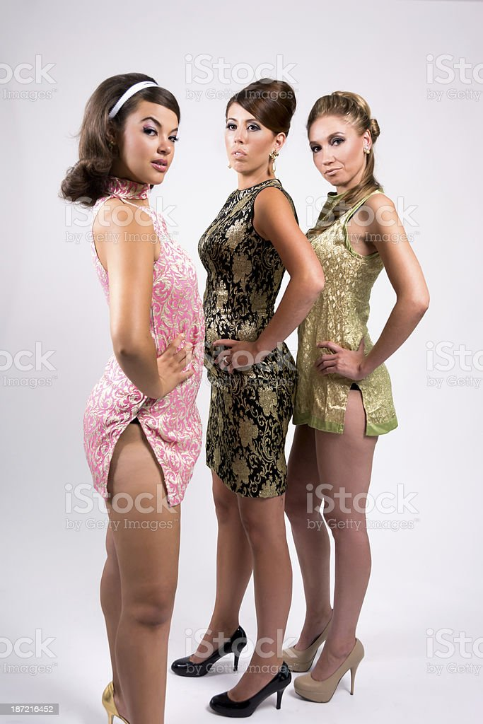 Trio of 1960s styled women with one standing closer. royalty-free stock photo