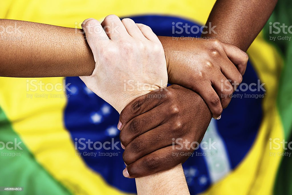Trio of Brazilian supporters clasp hands over national flag royalty-free stock photo