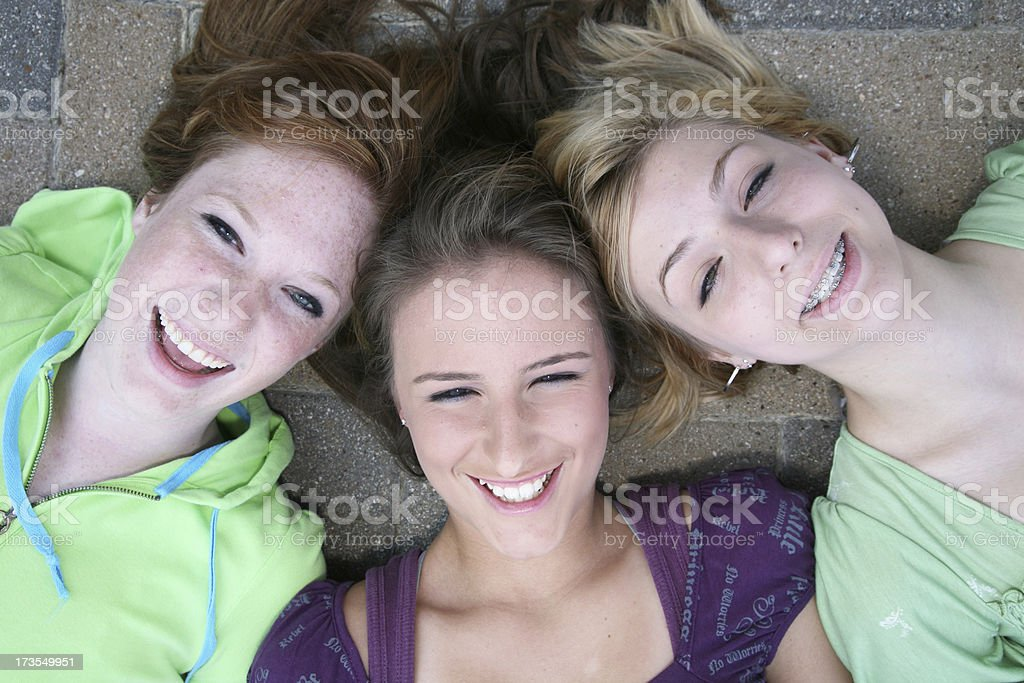 Trio of Friends Laying Down Taking A Picture Together stock photo