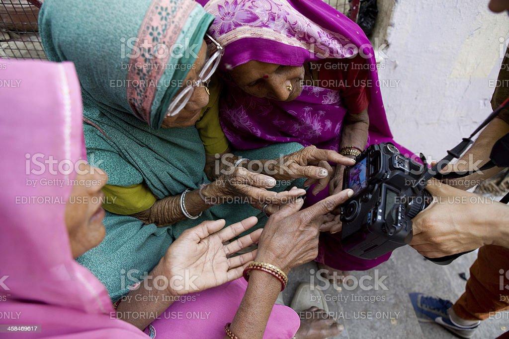 Trio of Indian women examining LCD camera stock photo