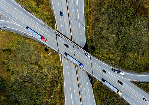 Looking down on a trio of semi trucks on a highway overpass.