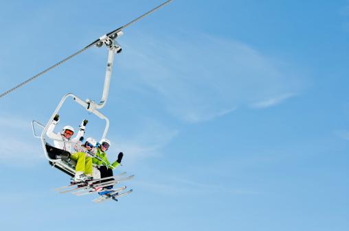 Trio of skiers riding on a ski lift