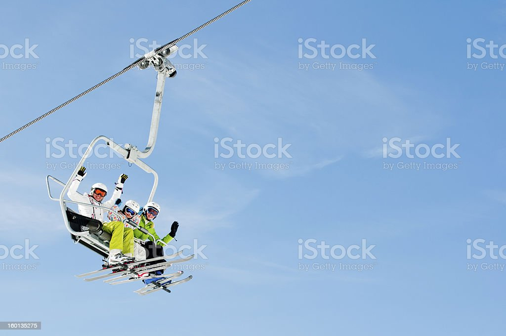 Trio of skiers riding on a ski lift stock photo