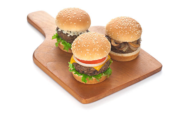 """Trio of Sliders on Cutting Board """"A trio of assorted sliders on a cutting board.  Sliders are classic cheeseburger; goat cheese and mixed greens; and mushroom, Swiss and onion."""" slider burger stock pictures, royalty-free photos & images"""