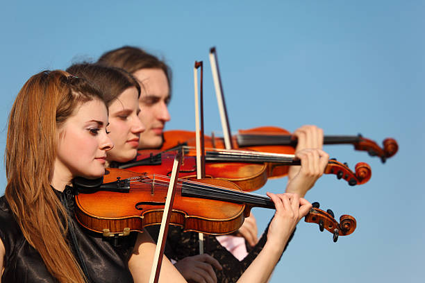 Trio of violinists plays against sky stock photo
