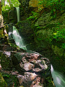 Wet moss covered rocks glisten in the sun as a brook tumbles down a rocky outcrop creating three waterfalls