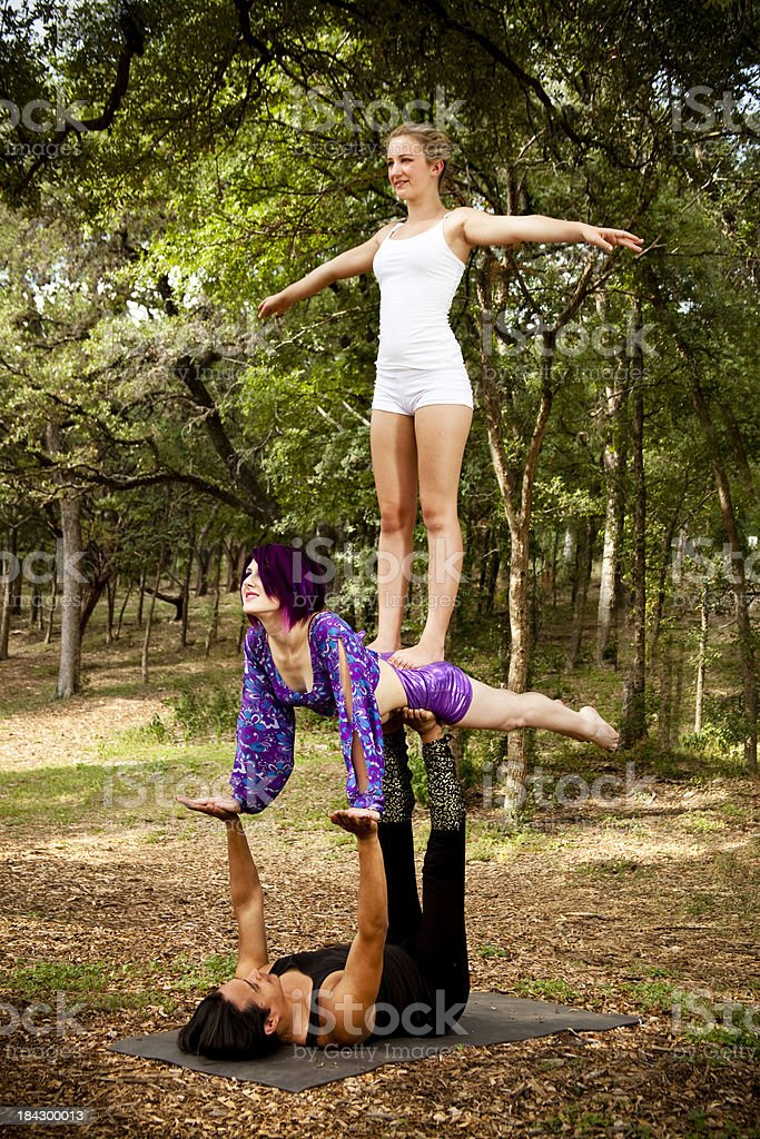 Trio performing AcroYoga in a secluded wooded area. royalty-free stock photo