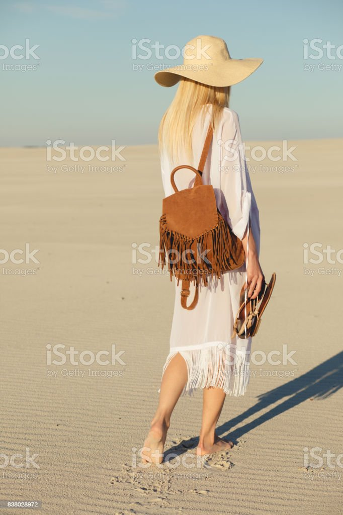 Trip alone. Woman walking away on a sand in desert. stock photo