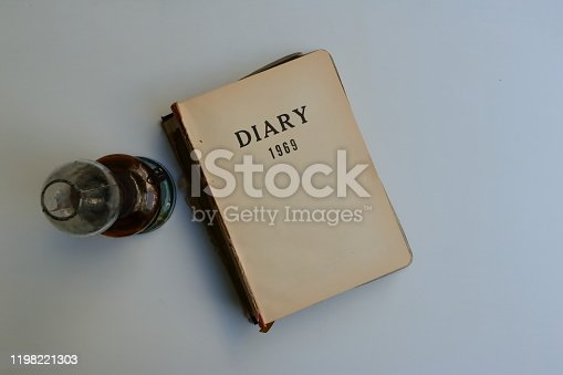 Closeup and focus on words DIARY 1969 of vintage diary with damaged spine placed on white wooden background next to antique kerosene lamp, a trip down memory lane concept