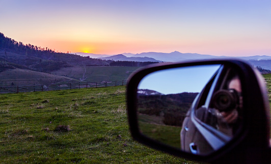 Sunrise in the Carpathian mountains. The reflection of the photographer with a camera in the mirror car in the foreground