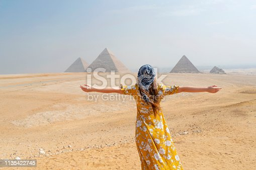 Rear view of a female tourist enjoying a tour to the Pyramids of Giza in Egypt.