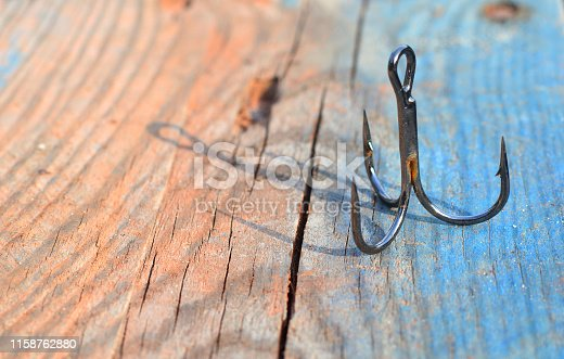 1094918172 istock photo Triple fishing hook on a wooden background. Fishing background wallpaper. 1158762880