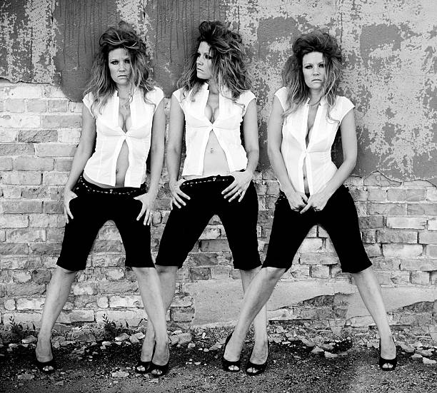 triple shots of woman posing against cement wall - triplets stock photos and pictures