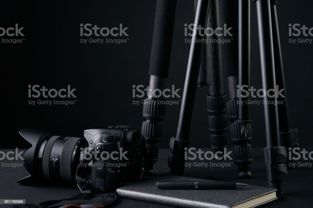 Tripods,notebook,pen and camera. stock photo