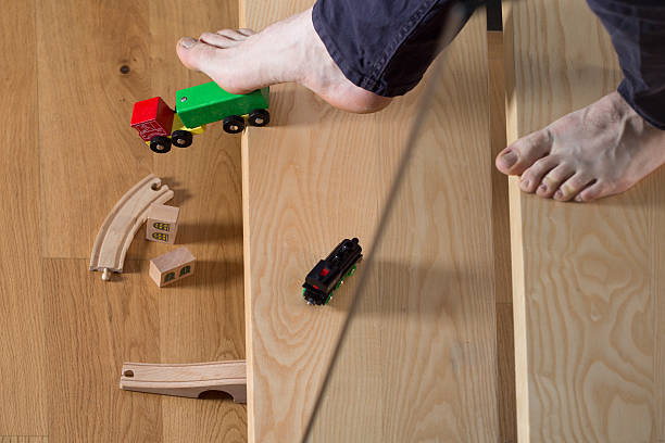 Tripped over child's toy Close-up of man tripped over child's toy kids cleaning up toys stock pictures, royalty-free photos & images